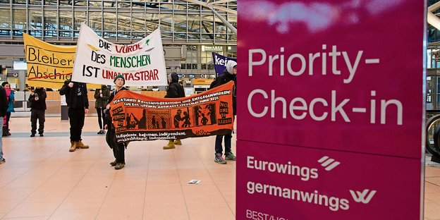 Ein violettes Priority-Check-In-Schild, daneben DemonstrantInnen