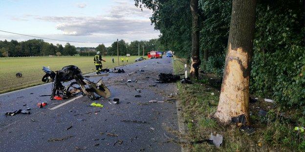 Rettungskräfte nach einem Unfall auf einer Straße, Blech liegt herum