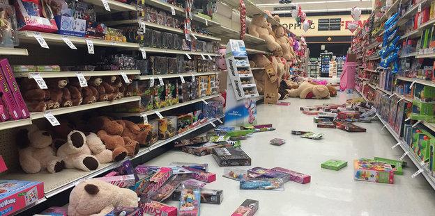 In einem Supermarkt ist Spielzeug aus den Regalen gefallen und liegt auf dem Boden verteilt herum