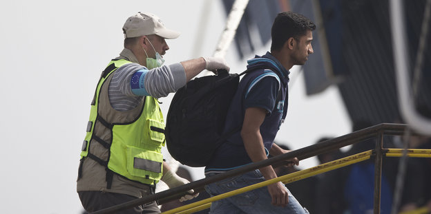 Ein Mann in Uniform geleitet einen anderen Mann an Bord einer Fähre