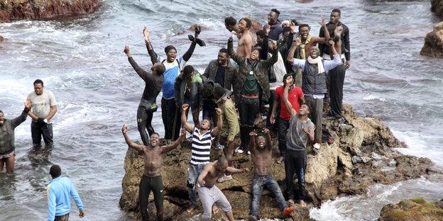 Menschen stehen auf einem Fels in der Brandung