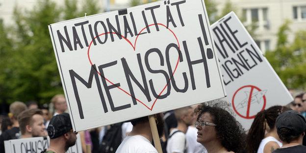 """Eine Demonstrantin vom """"Zug der Liebe"""" hält ein Transparent in die Luft. Darauf steht: """"Nationalität Mensch""""."""