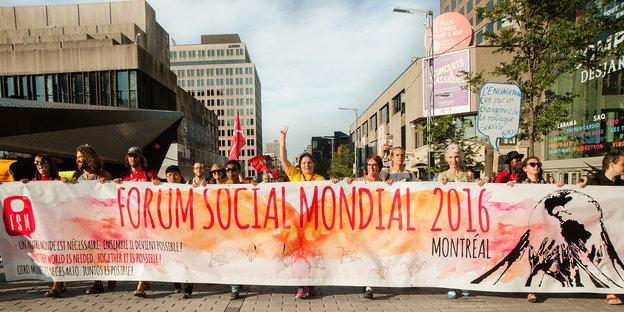 Menschen tragen ein Banner durch die Straßen einer Stadt