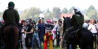 Zwei Polizisten zu Pferd stehen einer Menschenmenge gegenüber, die teilweise verkleidet ist