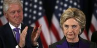 Hillary Clinton blickt streng, Bill Clinton applaudiert