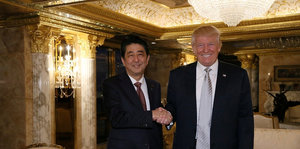 Shinzo Abe und Donald Trump in goldenem Ambiente