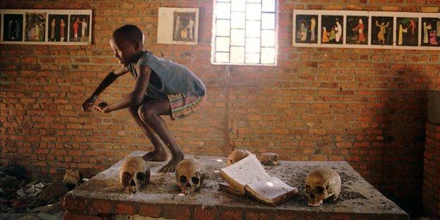 Im Innern einer verlassenen Kirche. Ein Kind springt auf einem Altar herum, auf dem Totenschädel liegen