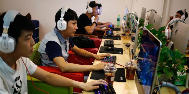 Chinesen sitzen nebeneinander in einem Internet-Café vor Computern