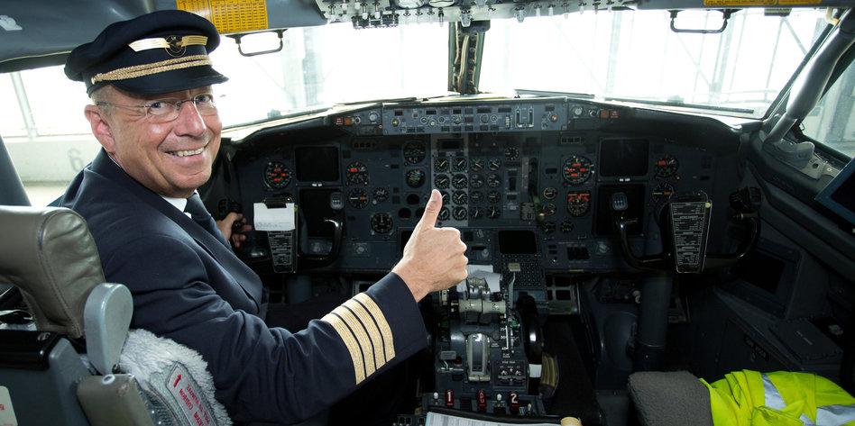 ein pilot im cockpit mit erhobenem daumen - Lufthansa Bewerbung Pilot