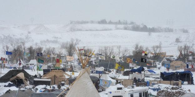 Zelte stehen auf einer schneebedeckten Fläche.