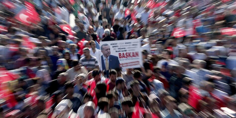 Flu bir insan topluluğu içinde bir Erdoğan afişi