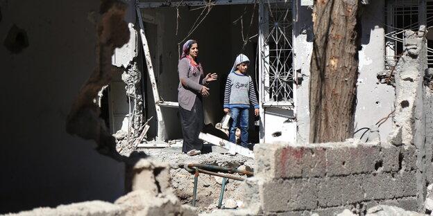Eine Frau und ein Kind stehen vor den Trümmern eines Hauses in der kurdischen Stadt Cizre