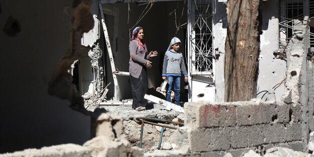 Sokağa çıkma yasaklarının ardından Cizre'de yıkılmış bir evden dışarıya bakan anne ve çocuk