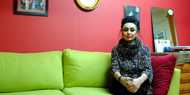 Eren Keskin auf einem grünen Sofa
