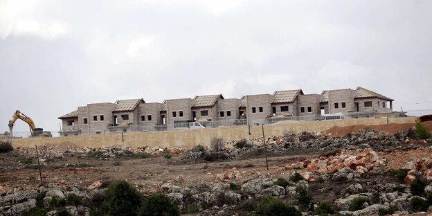Eine Häuserfront auf einem Hügel. Daneben steht ein Kran