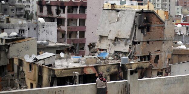 Eine Frau steht auf dem Dach und schaut sich die Trümmer ihrer Stadt