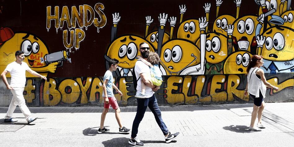 Graffiti in Istanbul: Gelbe Smileys werden bedroht und halten die Hände hoch. Vor der Wand läuft ein Mann mit einem Kind im Arm, der in die Kamera grinst.