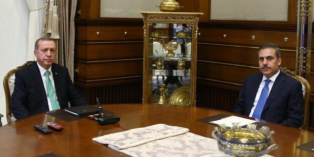 Zwei Männer in Anzügen sitzen an einem hölzernen Tisch, im Hintergrund eine prunkvoll gefüllte Vitrine