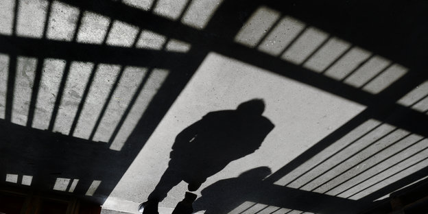 Der Schatten einer Zellenwand und eines Inhaftierten auf Beton