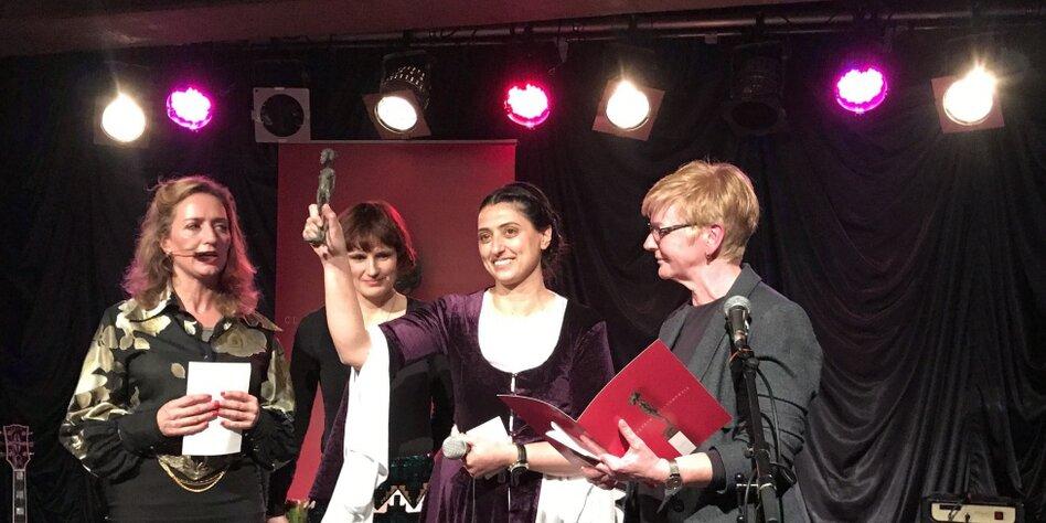 Feleknas Uca auf der Bühne mit dem Clara-Zetkin-Frauenpreis in ihrer Hand.