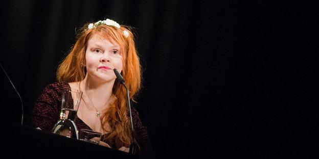 Eine Frau sitzt vor einem Mikrofon
