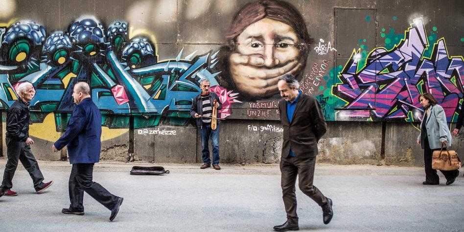 Ein Mann steht an einer Wand und spielt Kemence.
