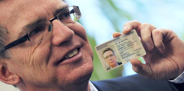 Bundesinnenminister Thomas de Maiziere hält seinen Ausweis in der Hand