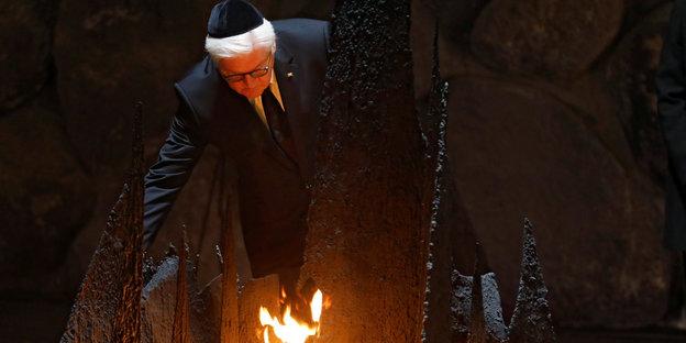 Steinmeier mit Kippa auf dem Kopf vor einer Flamme