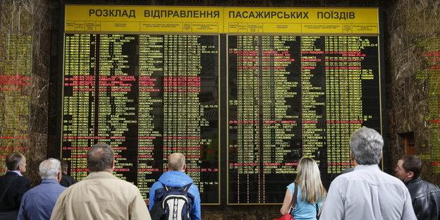 Menschen blicken auf eine Anzeigetafel auf einem Bahnhof