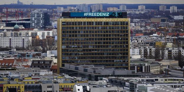 """An der Fassade eines Hochhauses steht """"Free Deniz"""""""