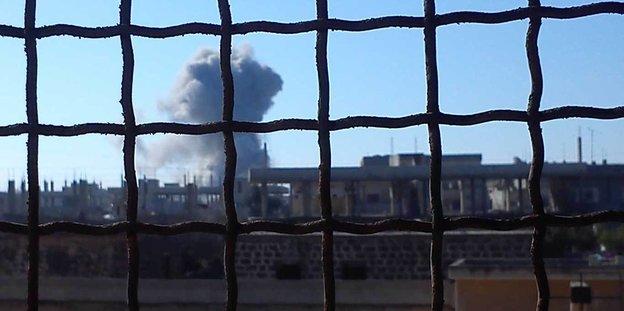 Filmausschnitt zeigt Rauchwolke über einer Stadt
