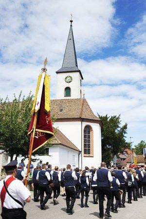 Eine Blaskapelle zieht an einer Kirche vorbei