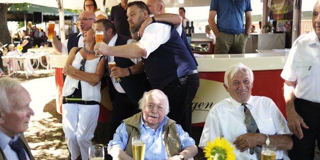 Drei ältere Männer sitzen an einem Tisch und trinken Bier, dahinter posieren Menschen vor einem Getränkestand für ein Foto