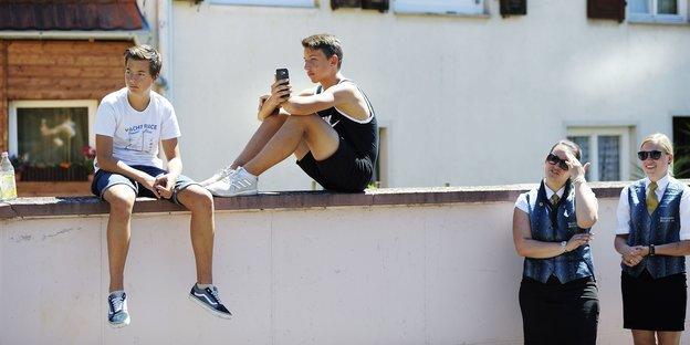 Zwei Jungs sitzen auf einer Mauer, daneben stehen zwei Mädchen