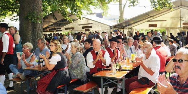 Etliche Menschen sitzen an Bierbänken und klatschen