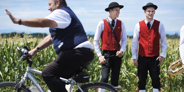 Zwei Männer in Tracht stehen vor einer Wiese, davor fährt ein Mann auf dem Fahrrad vorbei