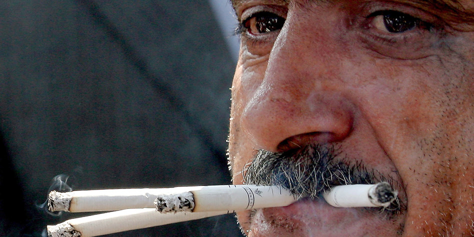 Ein Mann mit vier Zigaretten im Mund.