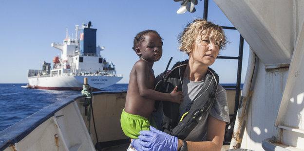 Eine Krankenschwester hält ein Kind auf dem Arm auf einem Schiff