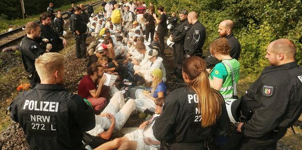 Menschen sitzen auf Gleisen. Davor einige Polizisten in Montur