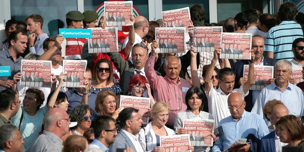 Eine Menschenmenge protestiert mit Ausgaben der Cumhuriyet