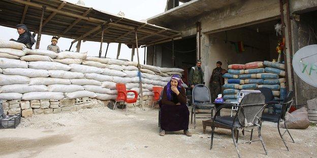 Eine Frau sitzt auf einem Stuhl, hinter ihr stehen Soldaten