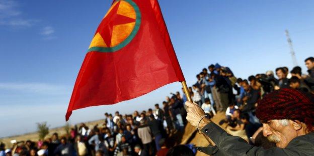 Ein Mann hält eine Fahne der YPG in die Höhe, hinter ihm eine Menschenmenge