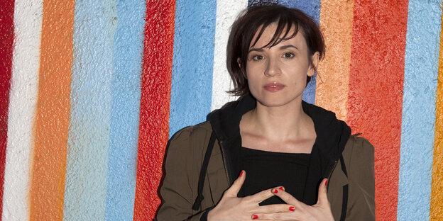 Eine Frau mit kurzen dunklen Haaren steht vor einer bunt gestreiften Wand