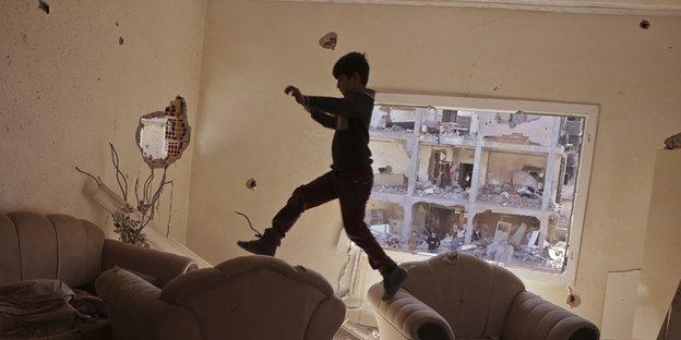 Eine Junge springt in einer Wohnung