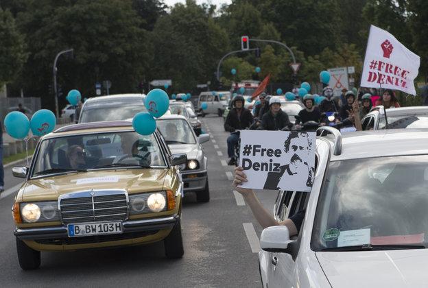 Autos fahren. Menschen halten Ballons und Schilder mit der Aufschrift FreeDeniz aus den Fenstern
