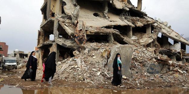 Ein zerstörtes Haus, davor vereinzelte Menschen und eine große Pfütze