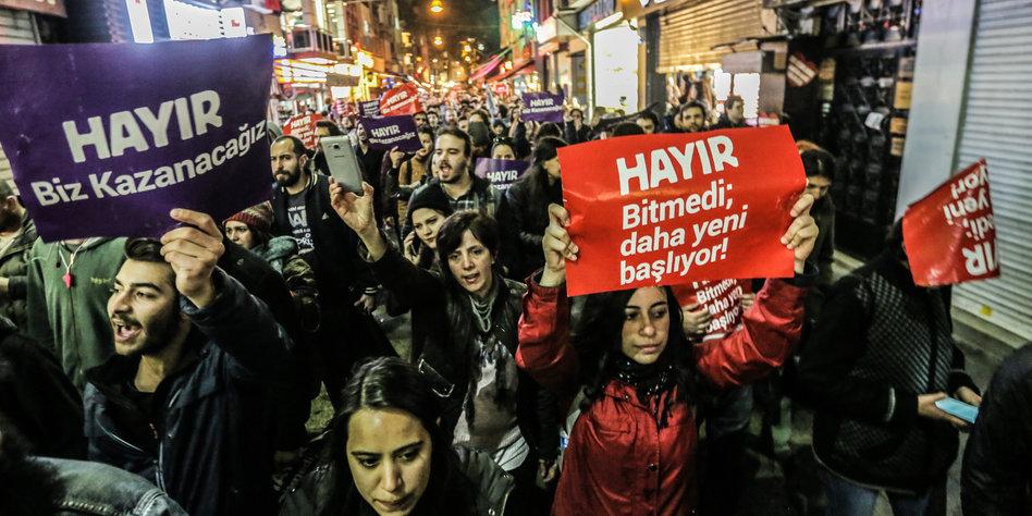 Demonstranten auf einer abendlichen Straße, die Plakate hochhalten