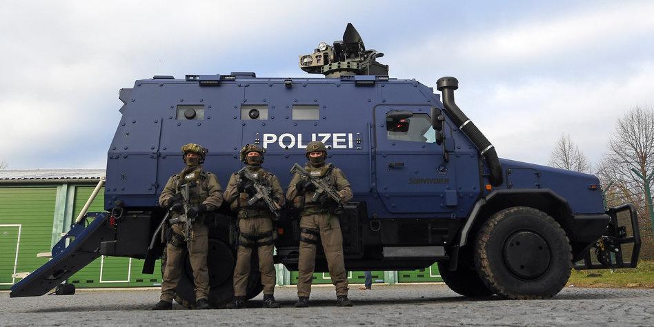 Bewaffnete Polizisten des SEK stehen vor dem Panzerwagen