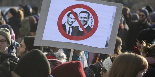 Ein Demonstrierender hält beim Protest gegen die neue österreichische Regierung ein Schild hoch, auf dem Bundeskanzler Kurz und Vizekanzler Strache durchgestrichen sind.