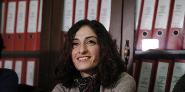 Meşale Tolu sitzt lächelnd vor einem Bücherregal